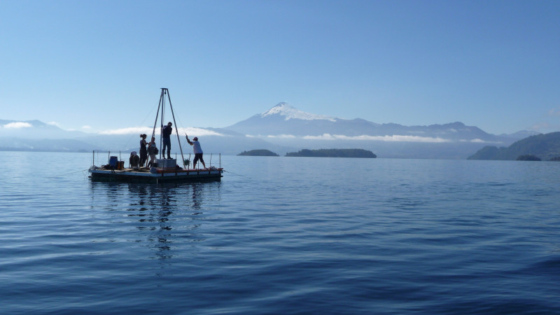 Caption:   Researchers taking sediment cores on Chilean lake Calafquén (with Vil